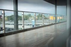 Lange gang met hardhoutvloer en parkeerterreinachtergrond Stock Afbeelding