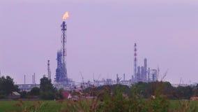 Lange gasgloed van raffinaderijinstallatie dichtbij groen gebied stock video