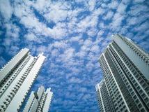 Lange gebouwen tegen een bewolkte blauwe hemel stock foto