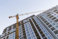 Lange gele bouwkraan tegen een blauwe hemel stock fotografie