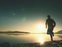 Lange geschikte mens die snel door het overzees op het strand lopen Krachtige agent opleiding openlucht in de zomerochtend Stock Foto