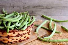 Lange grüne Bohnen in einem braunen Weidenkorb auf einem hölzernen Brett und einem Leinwandgewebe Hölzerner Hintergrund der Weinl Stockbild