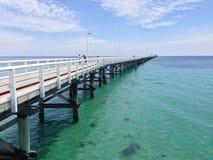 Lange hölzerne Anlegestelle, die über Ozean ausdehnt lizenzfreies stockfoto