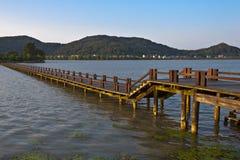 Lange hölzerne Brücke über einem Fluss Lizenzfreies Stockfoto