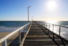 Lange hölzerne Strand-Anlegestelle im starken Tageslicht. Lizenzfreie Stockbilder