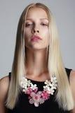 Lange Haar-Blondine mit frühlingshafter Girlande auf ihrem Hals Lizenzfreies Stockfoto