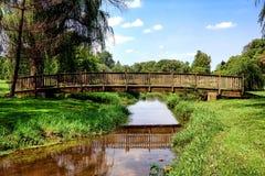 Lange hölzerne Fuß-Brücke über ländlichem Land-Strom Stockfoto