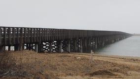 Lange Holzbrücke, die in den Nebel über Wasser im Winter einsteigt Stockbild