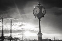Lange Klok tegen een Zonnestraalhemel Stock Afbeelding