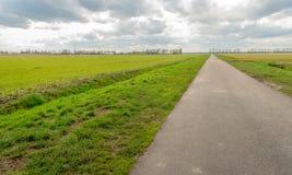 Lange landweg in een landelijk landschap stock fotografie