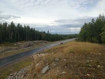 Lange manierweg Afstand, asfalt, hemel Laat ` s de weg raken! Een weg verdwijnt binnen aan de brede open blauwe hemel, weg, wegth Stock Foto