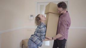Lange mens die zich in de ruimte met grote doos in handen bevindt De vrouw neemt de dozen van haar echtgenoot en brengt hen in hu stock videobeelden