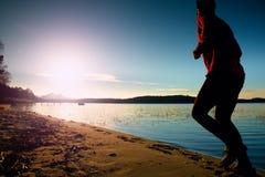 Lange mens in sportkleding bij verbazende zonsondergang in sport en gezond levensstijlconcept en het aanstoten van dwars de oplei Royalty-vrije Stock Afbeelding