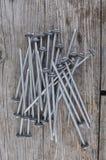 Lange metaalspijkers op een grijze houten lijst Stock Foto