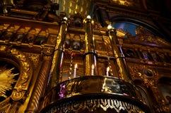 Lange Metallkerzenständer, die leuchtende Lampen und kleine klassische Kerzen unter ihnen in bulgarischer Kirche St. Stepen in I lizenzfreie stockfotos