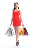 Lange mit Beinen versehene junge Frau, die mit Einkaufenbeuteln geht Stockfotografie