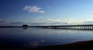 Lange pier in schemer en kalme wateren stock foto's