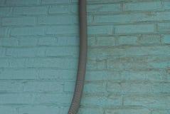 lange plastic slang op de groene bakstenen muur van het huis stock fotografie