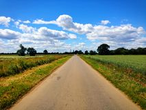 Lange, rechte landweg met gebieden en blauwe hemel in Lincolnshire, Engeland stock fotografie