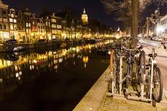 Lange Reihe von den Häusern, die in einem Kanal in Amsterdam sich reflektieren Stockfotos