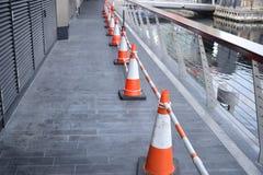 Lange Reihe von orange und weißen Kegeln auf einer niedrigen Brücke Lizenzfreie Stockbilder