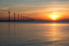Lange Reihe von windturbines mit Sonnenuntergang über dem Meer Stockfotografie