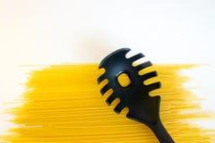 Lange rohe gelbe Spaghettis mit schwarzem Plastiklöffel mit dem Loch lokalisiert auf Weiß lizenzfreies stockbild