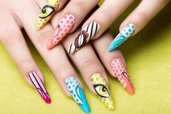 Lange schöne Maniküre in der Pop-Arten-Art auf weiblichen Fingern Nageldesign Nahaufnahme stockfoto