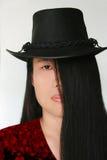 Lange Schönheit des schwarzen Haares mit Hut Stockfotos