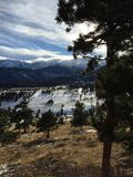 Lange schaduwen, bomen, en wolken over sneeuw afgedekte bergpieken royalty-vrije stock foto