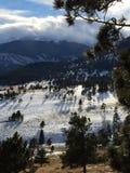 Lange Schatten, Bäume und Wolken über Schnee bedeckten Bergspitzeporträtart mit einer Kappe Lizenzfreies Stockfoto