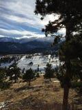 Lange Schatten, Bäume und Wolken über Schnee bedeckten Bergspitzen mit einer Kappe Lizenzfreies Stockfoto
