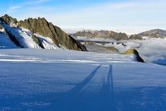 Lange Schatten von zwei Personen auf dem Gletscher du Tour stockfotos