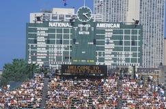 Lange Sicht der Anzeigetafel und der vollen Zuschauertribünen während eines Spiels des professionellen Baseballs, Wrigley fangen, Stockbild