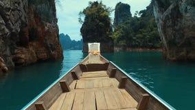 Lange staartboot op het meer in de rotsen stock footage