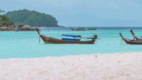 Lange staartboten die in blauw water met wit zandstrand slingeren vooraan wachten voor toerist, Koh Lipe-eiland, Thailand stock video