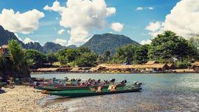 Lange staartboten op zonsondergang bij Liedrivier, Vang Vieng, Laos stock foto's