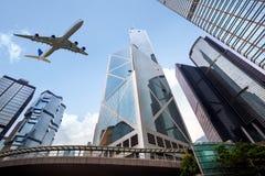 Lange stadsgebouwen en een vliegtuig die boven vliegen Royalty-vrije Stock Fotografie