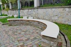 Lange steenbank in het park stock afbeeldingen