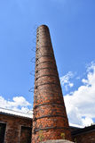 Lange uitstekende die fabrieksschoorsteen van rode bakstenen met metaal wordt gemaakt ledder Stock Foto