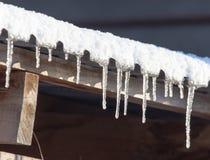 Lange und gefährliche Eiszapfen auf einem Hausdach stockfotos