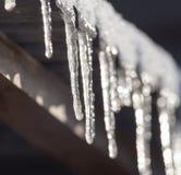 Lange und gefährliche Eiszapfen auf einem Hausdach lizenzfreies stockfoto