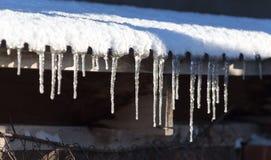 Lange und gefährliche Eiszapfen auf einem Hausdach stockfotografie