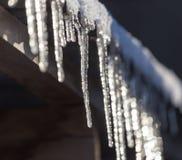 Lange und gefährliche Eiszapfen auf einem Hausdach stockbilder