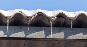 Lange und gefährliche Eiszapfen auf einem Hausdach lizenzfreie stockbilder