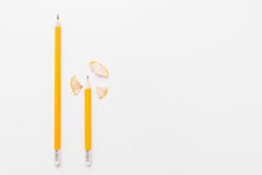 Lange und kurze Bleistifte mit Schnitzeln auf Weiß Lizenzfreie Stockfotografie