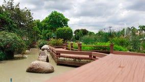 Lange Vision der hölzernen Wegweise mit Landschaft des Gartens Lizenzfreie Stockfotografie