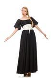 Lange vrouw in lange zwarte die kleding op wit wordt geïsoleerd Stock Foto