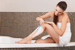 Lange vrouwenbenen Vrouw het scheren benen in badkamers Stock Foto's