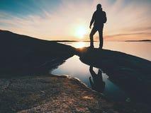Lange wandelaar in donkere sportkleding met rugzaktribunes op klip boven overzees De mens geniet van verbazend zonsondergang Royalty-vrije Stock Foto